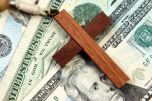 A wooden cross over a stack of money with the words in god we trust besides it.